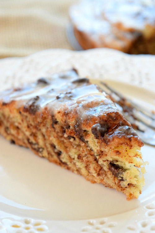 Slice of Chocolate Cinnamon Roll Cake with Orange Icing.
