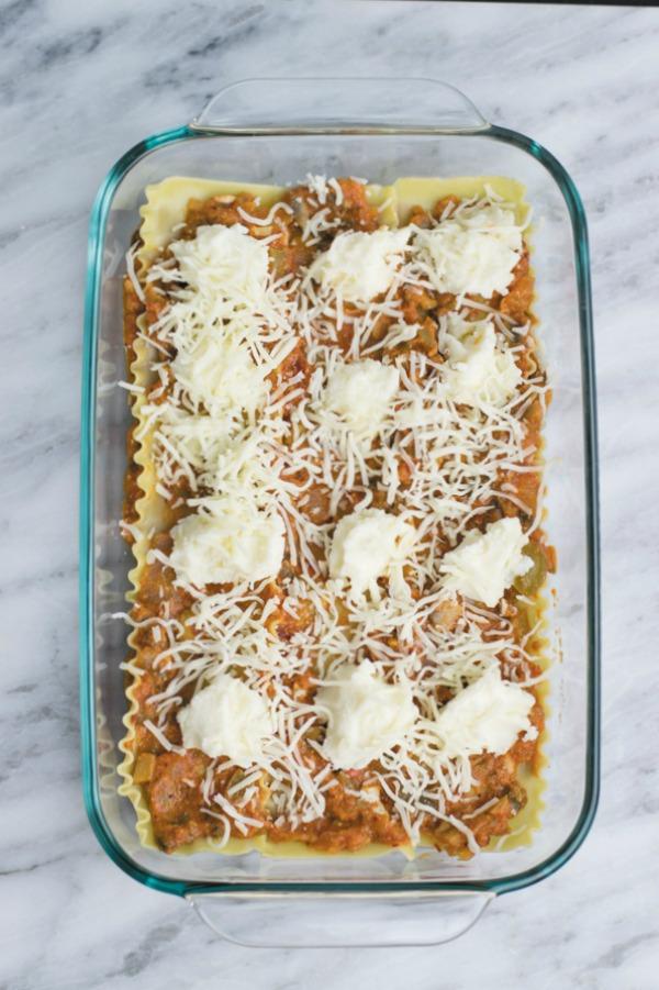 spreading shredded cheese for easy vegetarian lasagna